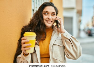 Young middle east woman talking on the smartphone drinking coffee at the city.