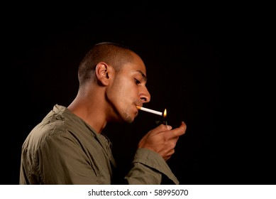 Young middle eastern man lighting a cigarette