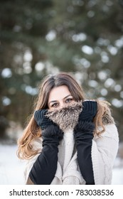 Young middle eastern woman wearing a sweater and gloves.