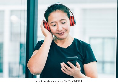 Young middle-aged athletes are listening to music from smartphones using wireless headphones after she is tired of exercising at the fitness center. Concepts about health and leisure care.