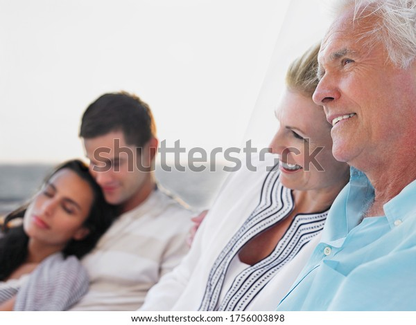 Young and middle-aged couple relaxing on yacht focus on middle-aged couple