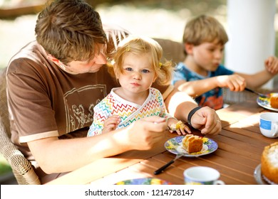 Young middle-aged father feeding cute little toddler girl in restaurant. Kid boy eating on background. Happy healthy family in an outdoor cafe in summer time, eating cake