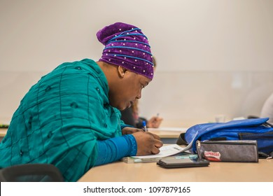 young migrant woman from Africa in national clothes is trained in German at a language school in Halle (Saale), Germany, May 24, 2018