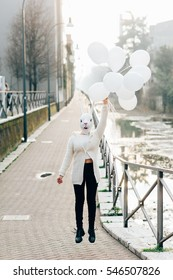 Young milennial woman wearing rabbit mask holding white balloon - carneval, dreamlike, surreal concept
