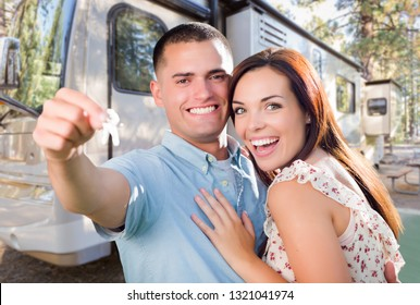 Young Military Couple Holding In Front of New RV.