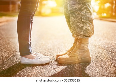 Young military couple kissing each other, homecoming concept, soft focus,warm orange toning applied
