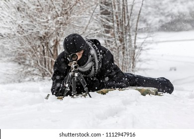 A young military man training to shoot a weapon during a snowstorm in an outdoor environment.