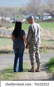 Young military man and young woman holding hands and saying goodbye.