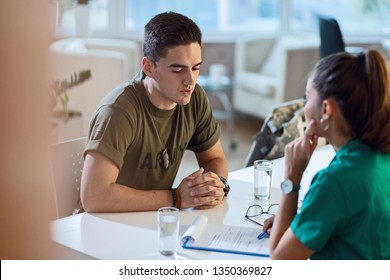 Young military officer having an appointment with psychotherapist at doctor's office.