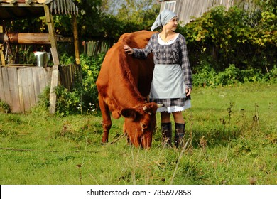 young milkmaid in a field with a cow