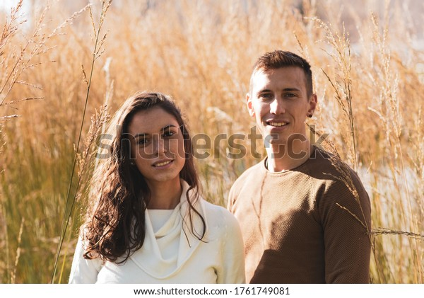 young millenials man and woman posing for an outdoor photo portrait, natural environment with bushes of tall golden grass, sunset light