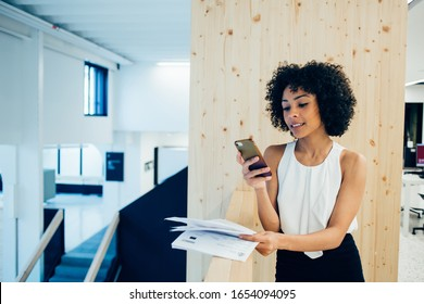 Young millennial african american female reading news from social networks via mobile phone standing in modern office, smiling dark skinned businesswoman in formal wear using smartphone and 4G