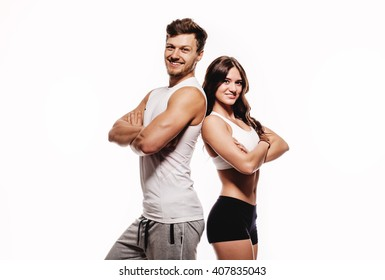 Young millennial beautiful athletic brunette woman and handsome man posing on white background studio shot. Wearing sport wear standing looking at camera smiling. Healthy positive cheerful people.