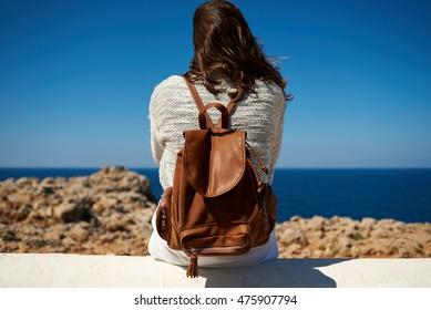 Young millennial brunette having fun in the coast line of a mediterranean island