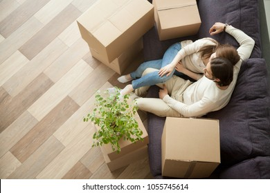 Young millennial couple owners moved into new home resting on couch on moving day, happy family with boxes relaxing on sofa in living room, easy relocation with delivery service concept, top view