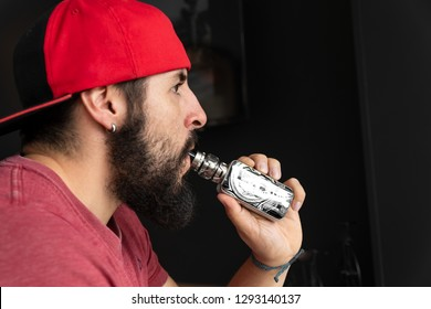 Young millennial enjoying his electronic cigarette, this vaping activity is very fashionable and is also used for people who want to quit smoking