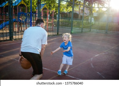 Young millennial father in his 30s playing basketball with his little baby girl daughter outdoor in a court in the evening