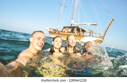 Young millennial friends taking selfie and swimming at sailing boat sea trip - Rich guys and girls having fun in summer party day - Exclusive vacation concept - Tilted horizon on bright warm filter