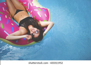 Young millennial girl in sprinkled doughnut float at pool, festival, hotel, beach, event smiling with sunglasses on during summer (with hipster matte texture)