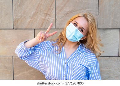 young millennial girl wearing her protective mask makes the sign of victory with one hand, smiling with the eyes, a concept of optimism during the period of a world pandemic