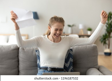 Young millennial happy woman sitting on sofa in living room at home. Laughing girl holds letter feels excitement and happiness. Smart student received scholarship, employee hired on good post concept
