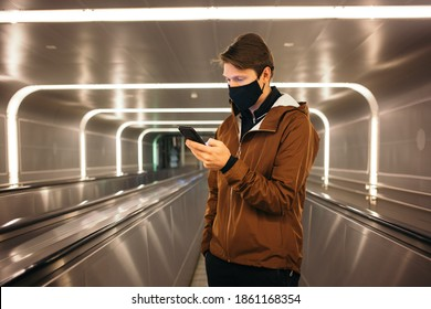 Young millennial man in casual outfit and black face mask travel on moving walkaway at train station or airport, use smartphone to use covid tracking app or stay up to date with world news