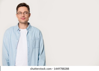 Young millennial man with cunning look isolated on grey background. Thoughtful mysterious male looking aside wearing glasses posing at studio. Advertising, blank, empty copy space banner concept