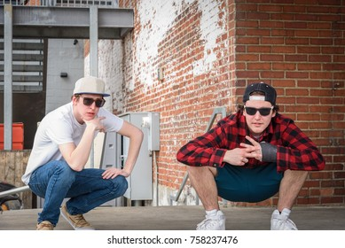 young millennial men in sunglasses and snap back caps posing and acting tough on loading dock with brick wall