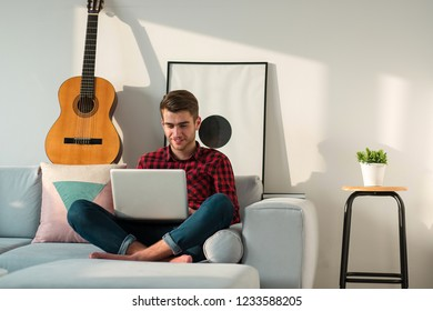 Young millennial positive man sitting on couch in living room with laptop alone on weekend at home