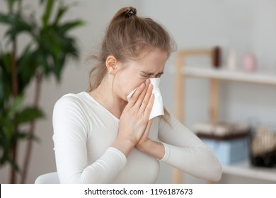 Young millennial sick woman sitting alone at work office sneeze holding tissue handkerchief and blowing wiping her running nose. Student girl has seasonal allergy or chronic sinusitis disease concept
