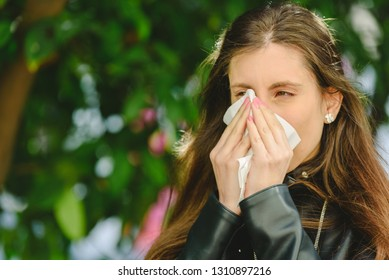 Young millennial sick woman sneeze holding tissue handkerchief and blowing wiping her running nose.