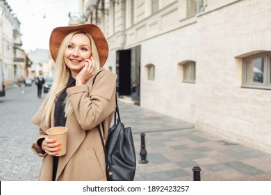 Young millennial smiling blonde woman dressed in autumn coat and hat. Cute girl talking on phone and holds cup of coffee on the go in European street.