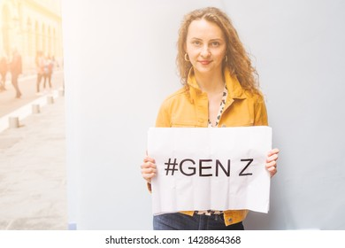 "Young millennial teenage with red hair and a funny expression ,making lips and winking, holds a sign with the text "" #genz"" written on against a city wall and light flares"