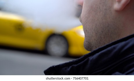 Young Millennial urban hipster man blowing vapor electronic cigarette smoke outside on New York City street in day time. Yellow taxi cab passes in background. POV over shoulder view