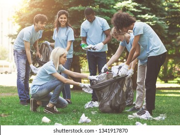 Young millennial volunteers picking garbage in park, ecology protection concept, free space