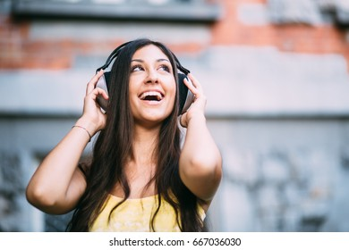Young millennial woman listening to music on the street