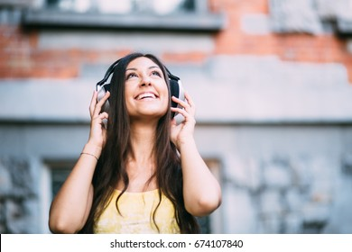 Young millennial woman listening to music on park bench