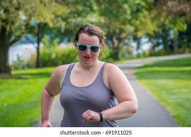 Young millennial woman running at the park tracking on her smartwatch