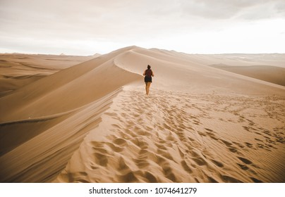 Young millennial woman tourist /  traveler walks out across a sand dune into the desert with a red backpack in Huacachina, Peru