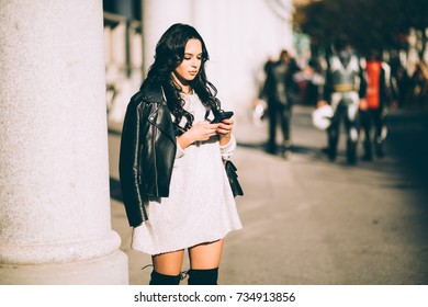 Young millennial woman using phone on street texting calling