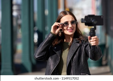 Young millennial woman vlogger recording daily video diary outdoors, online content creator for social media platforms
