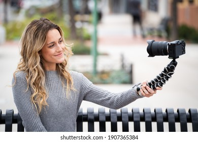 Young Millennial Women with Blonde Brunette Hair Vlogging at Mirrorless Camera on Tripod