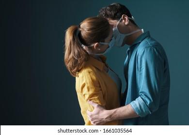 Junge Jahrtausende junge Paare, die Schutzmasken tragen und sich küssen, sich vorbeugend gegen Virusverbreitung und das Konzept der Menschen