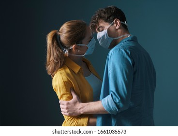 Young millennials couple wearing protective face masks and kissing each other, virus spread prevention and people concept