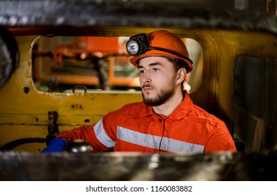 A young miner in a coal mine in the generals is busy working, repairing against the background of equipment. Portrait. the red form.