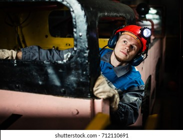 The young miner. Diesel locomotives for coal mining. Under the ground, work is being done, repaired against the backdrop of mining equipment.