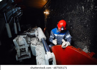 young miner man underground in a mine for coal mining in overalls is busy with work, repairing against the backdrop of equipment. Portrait.