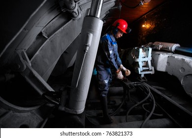Young miner works underground in a mine with mining equipment for coal, gold, minerals.