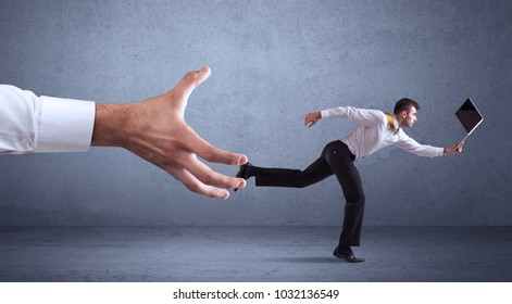 Young miniature businessman running from a big hand with blueish grey background