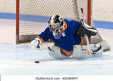 Young minor ice hockey goaltender making a save during a game